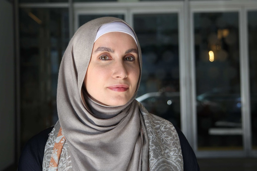 A woman in a hijab stands in front of a glass wall in the afternoon light.
