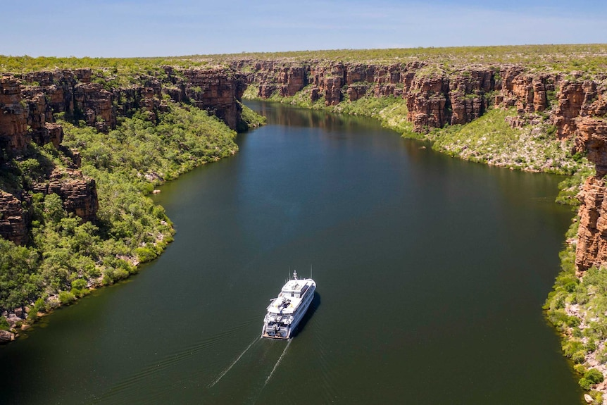 Image of a boat travelling up a river in a gorge with bushland on either side.