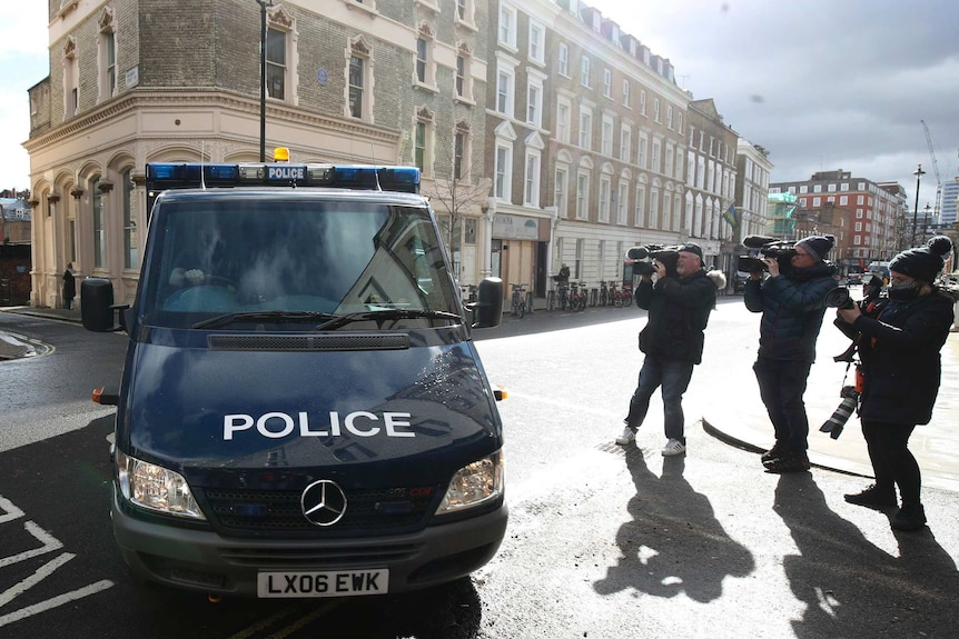 A police van drives past three camera operators as it turns into a court building off a London street.