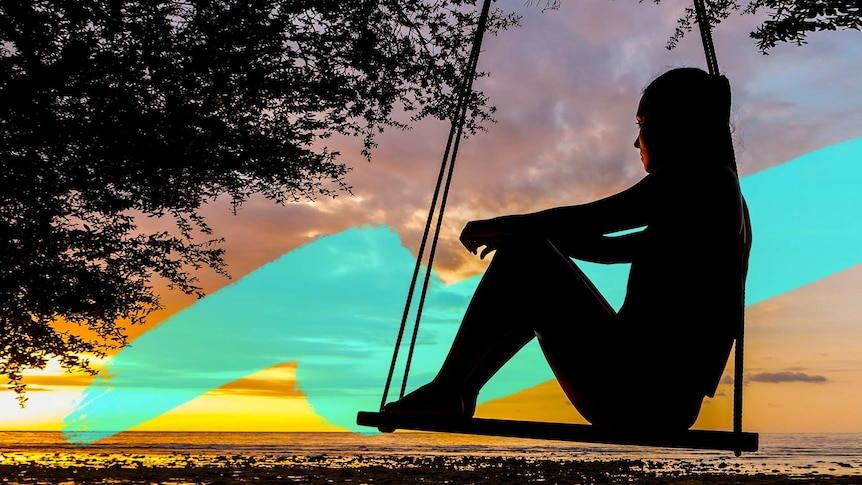 Silhouette of a woman on a swing that is hanging from a tree, with a sunset in the background