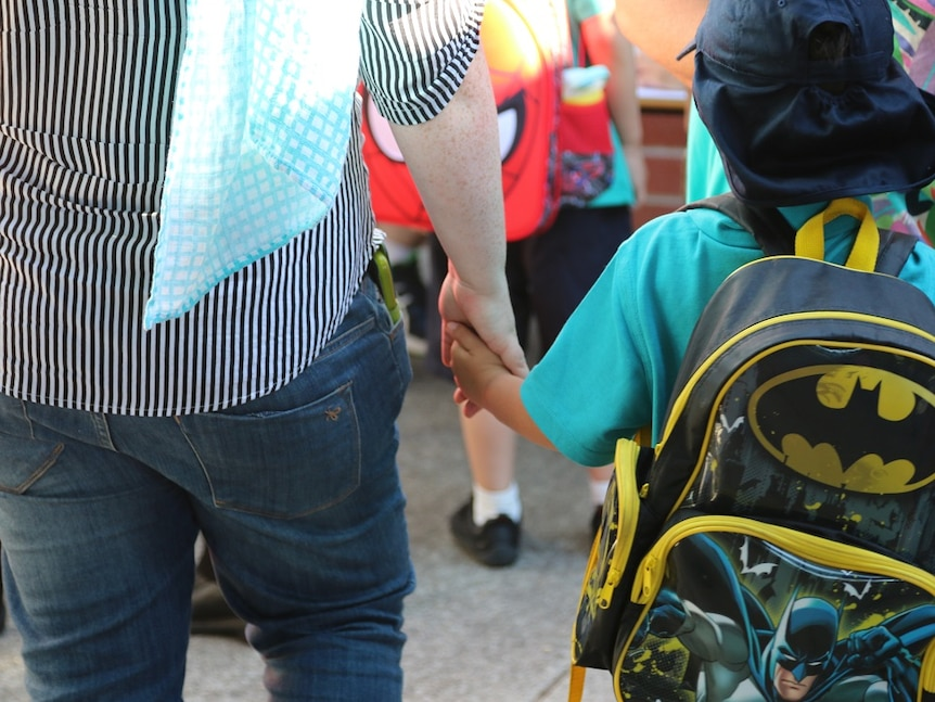 Young boy holds his parent's hand as he waits in line for his first day of kindergarten.