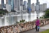 A woman wears a face mask walking along the Kangaroo Point Cliffs with city buildings in view in Brisbane