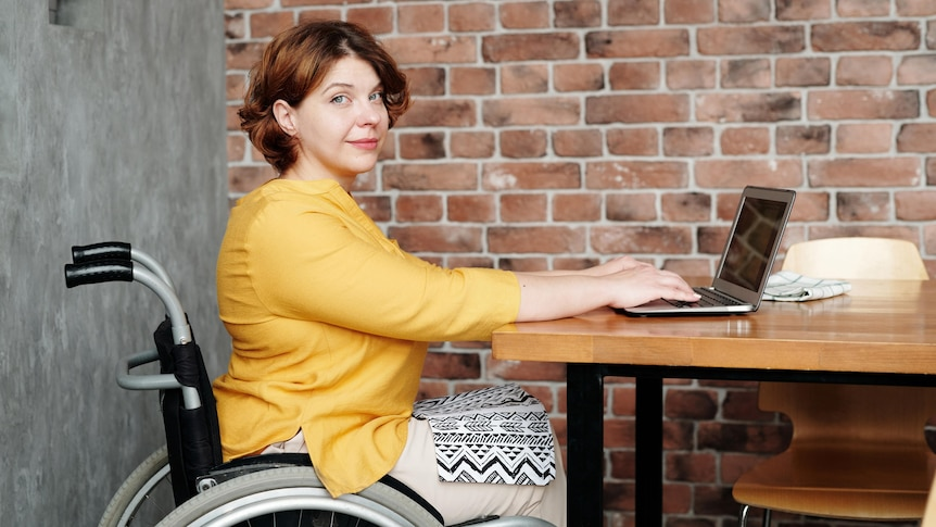 Woman working from home using a wheelchair, in a story about working from home long term.