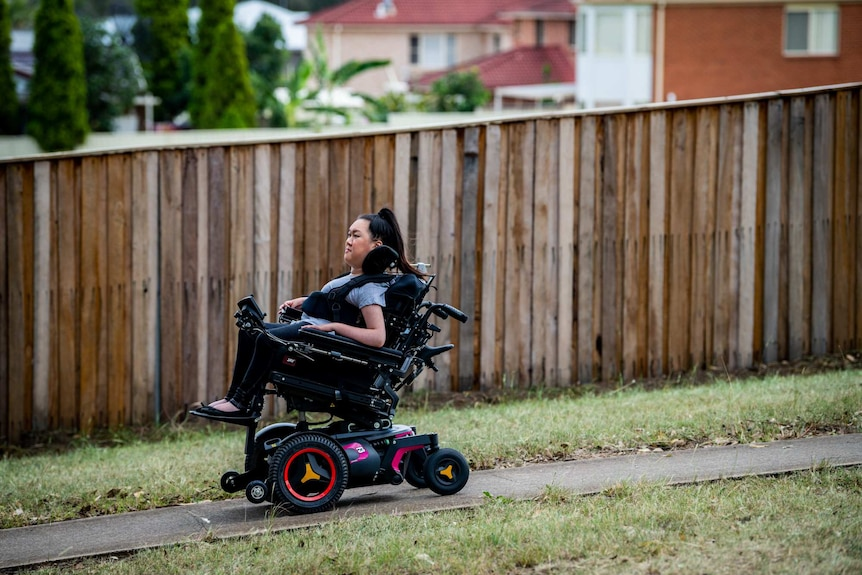 Melanie Tran goes downhill in her wheelchair, with a wooden fence in the background.
