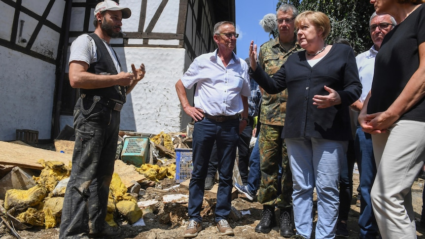 Angela Merkel speaks to a resident in a flood affected town