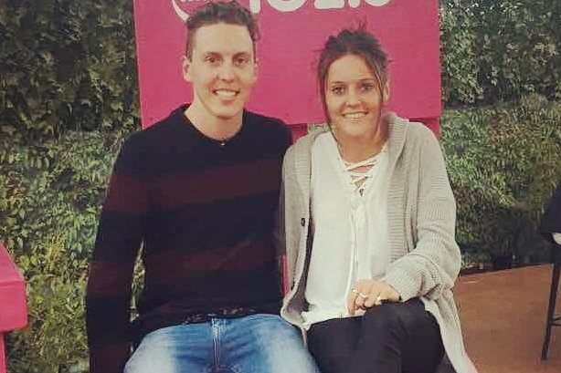 Hayley Raso and her brother Lachlan sit on a giant pink chair.