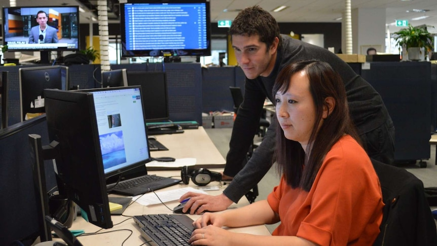 Wide shot of Viney and Zhou looking at computer screens in newsroom.