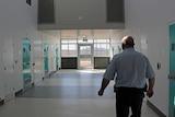 Prison guard walks along corridor at AMC past cells
