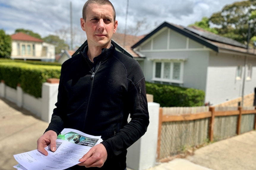 a man outside a house with energy bills in his hand looking unimpressed