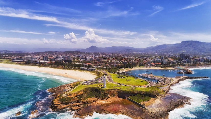 Aerial shot of Flagstaff Point lighthouse and breakwater with Wollongong city in the background.