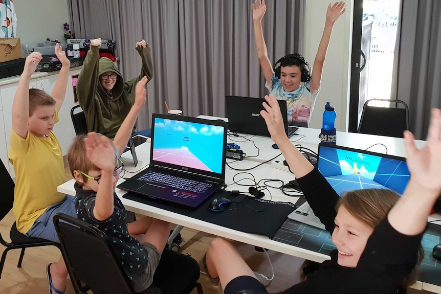 Group of autistic children around table with hands in the air excited to be learning gaming skills