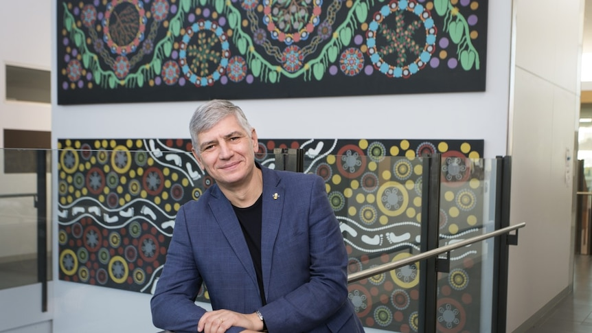 Mike Kyrios smiling at the camera with Aboriginal artwork hanging behind him
