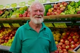 An older man stands in a store in front of fruit and vegetables.