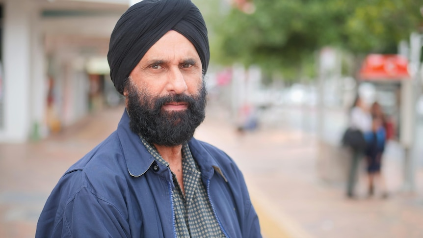 A man wearing a turban, standing on a street