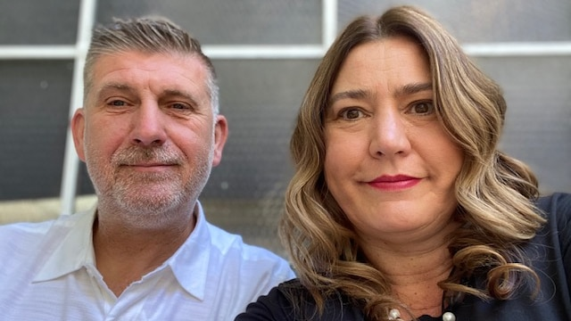 A man and a woman smile in a selfie.