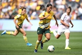 A footballer dribbles with the ball as she runs down the field in an international friendly.