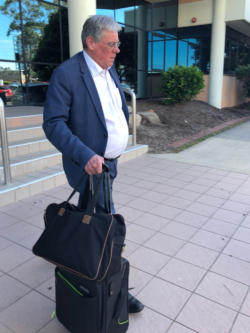 Man walking with luggage outside a court house