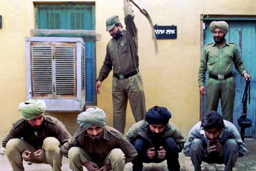 A police office wields a whip over four squatting men