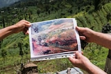 Photo of cleared plantation held in front of flourishing land to compare