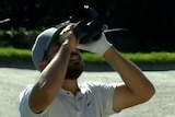 Jason Day looks up a the trees with some binoculars