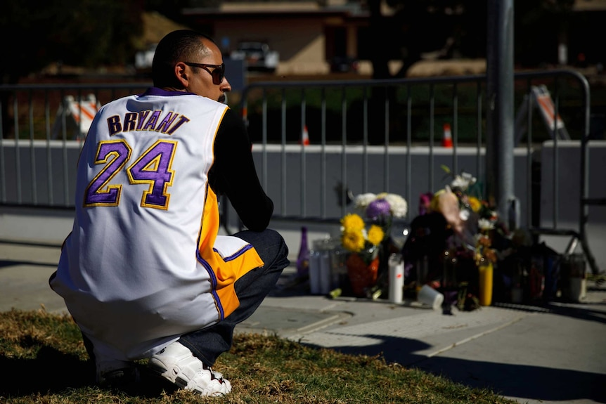 A man wearing a Kobe Bryant jersey crouches as he looks at floral tributes laid near the helicopter crash site.