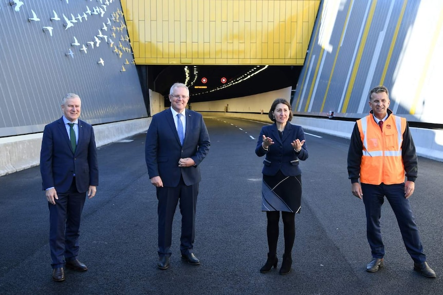 Four people outside a tunnel