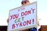 A woman holds a sign saying Netflix you don't get Byron
