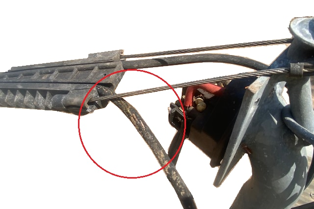 A computer-generated illustration of damaged insulation on an overhead powerline making contact with a wire.