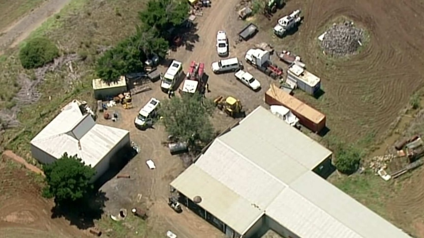 An aerial shot of a number of emergency vehicles parks outside a farm building.