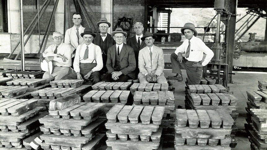 Men stand behind piles of lead bullion.