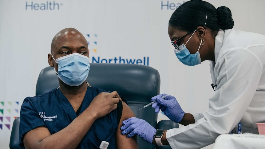An African American woman injecting a vaccine in the upper arm of an African American man