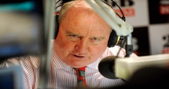A man talking into a microphone in a radio studio