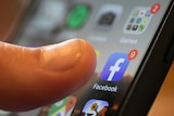 A finger touches the Facebook app on a smartphone