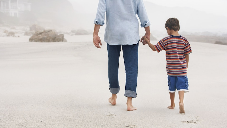 A father and son walk hand in hand on a beach