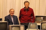 Two men stand behind a range of anique computers