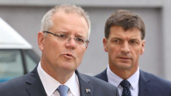 Scott Morrison speaks to media in Canberra as Angus Taylor, frowning, watches on.