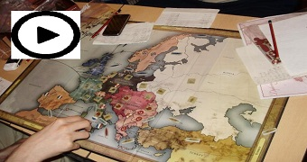 A man plays a board game that includes a world map.