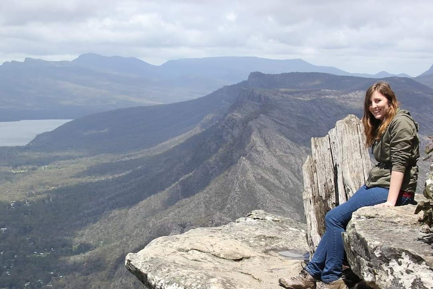 Woman in green jumper sits on giant rock, mountains in background.