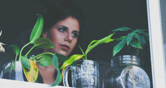 Woman with pot plants in front of her