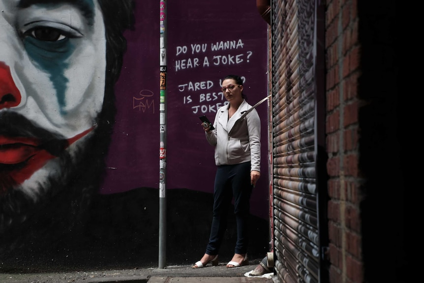 A picture of a woman holding a phone looking at the camera. Graffiti art on the wall behind shows a clown.