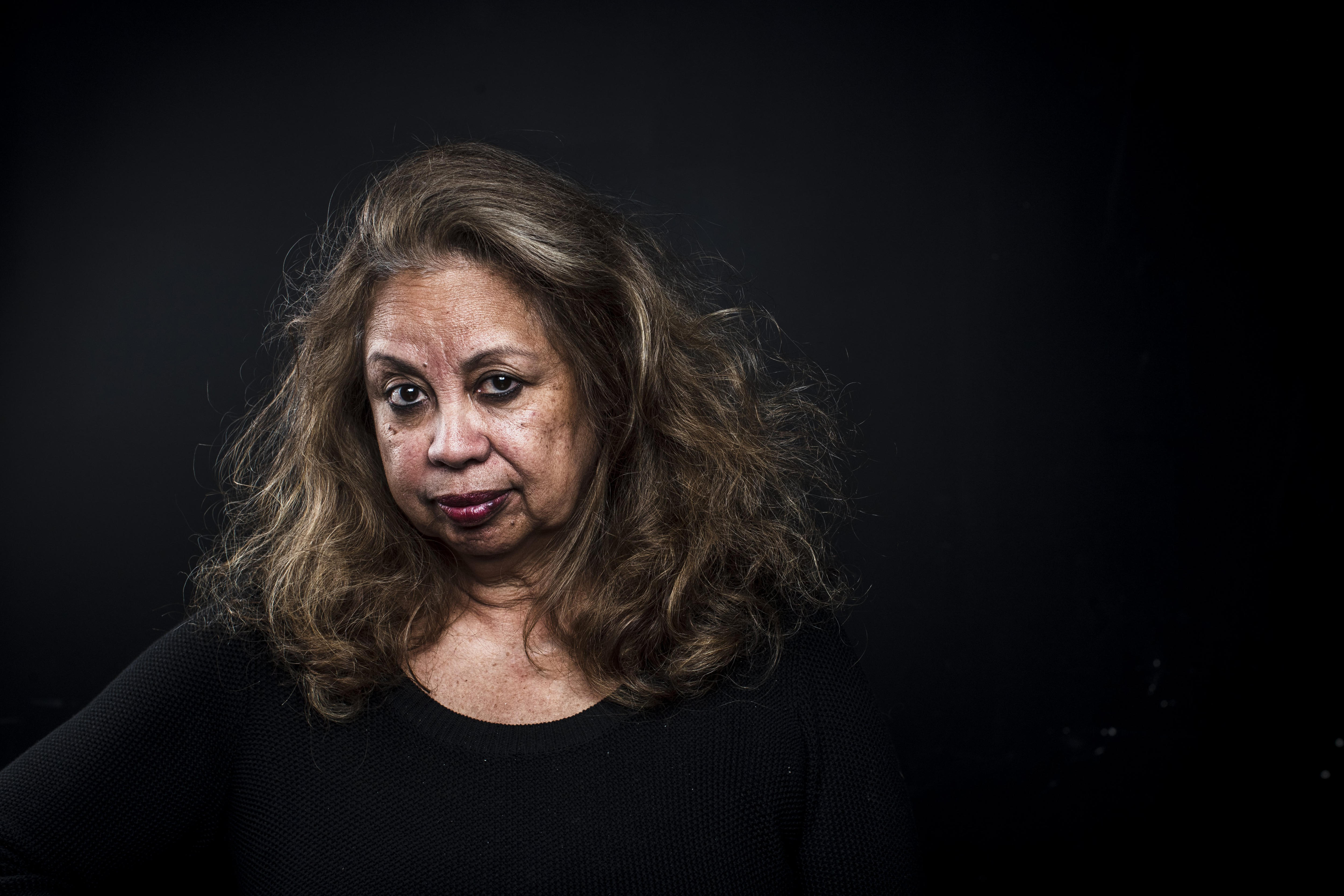 A portrait shows Dr Anae against a black background. Looking strong and straight at the camera.