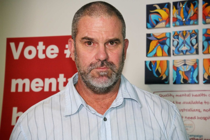 A man wearing a blue collared shirt looks into the camera