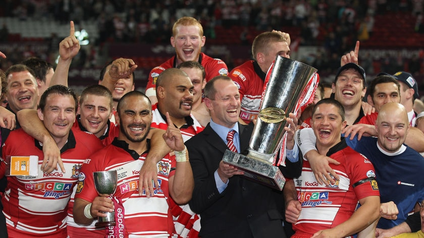 Wigan coach Michael Maguire lifts the Super League trophy at Old Trafford
