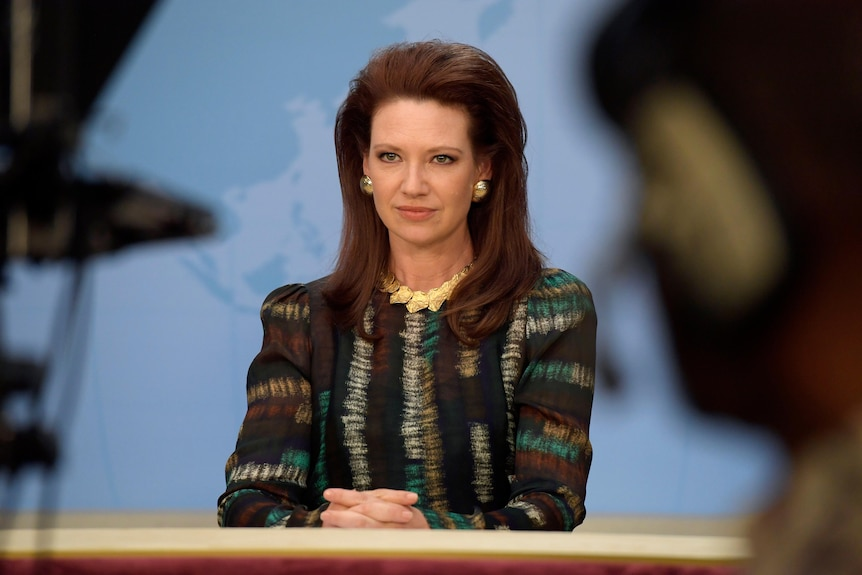 Still from a tv show, a female newsreader in 80s style sits as a desk on a tv set