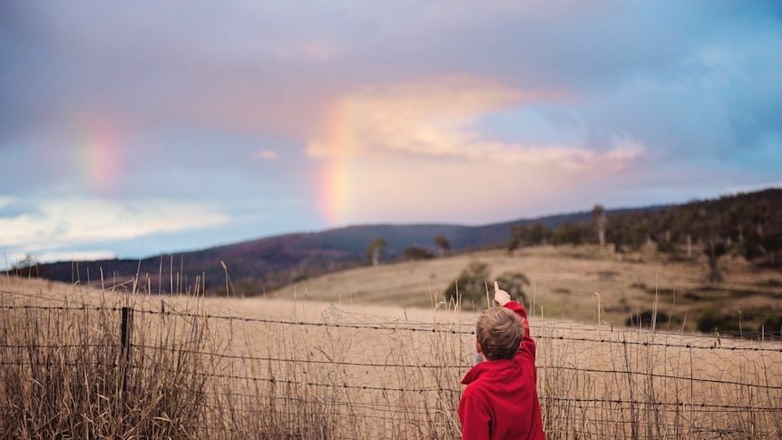 A young boy points at a rainbow beyond a fenced paddock