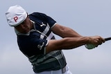 Bryson DeChambeau, wearing a white flat cap with a P on it, completes his swing as para gliders fill the sky behind him