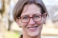 Tasmanian Greens leader, Cassy O'Connor Greens wearing glasses, smiles.