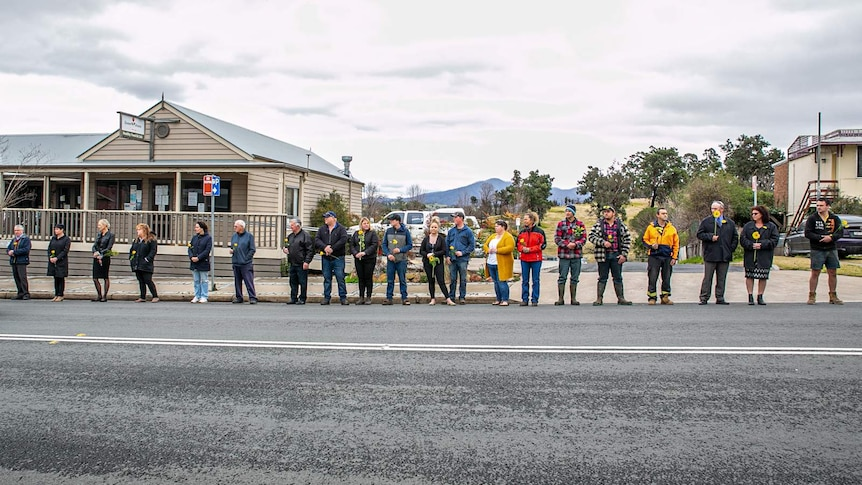 Men and women stand along street of small country town holding yellow flowers, spread evenly with 1 metre between them.