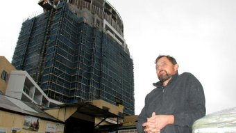 A man stands in front aof a large high-rise development.