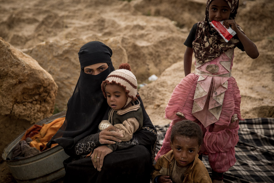 A woman and her children sit on the ground in the Khamer displacement camp in Yemen's Amran province.